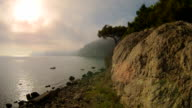 Beautiful sunset over the sea. Mountains and pine trees video