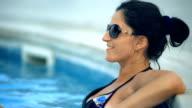Beautiful tanned woman relaxing in bikini and sunglasses in swimming pool video