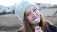 Beautiful teenage girl in a gray knitted cap, which showing and eating lollipop, artistic and expressive playing on camera, stock footage. video