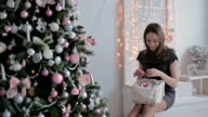 Beautiful teenager girl sorting out christmas balls and decorating the Christmas tree video