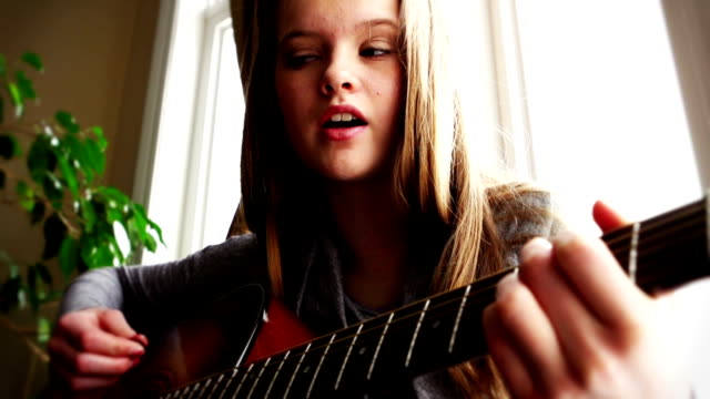 Beautiful teenager playing guitar video