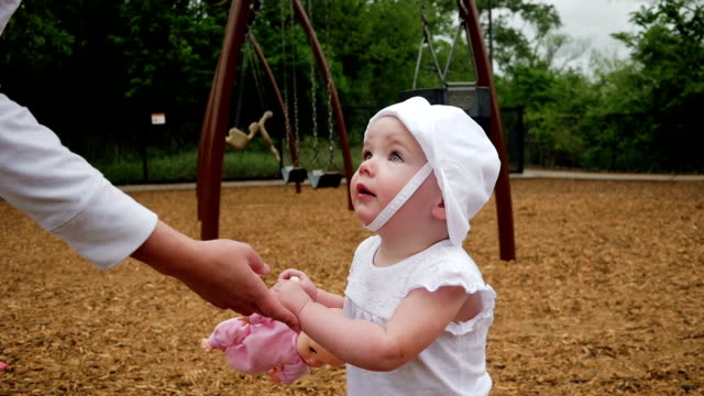 Beautiful toddler girl reaches for mom to pick her up at park video