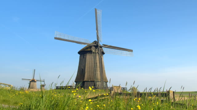 CLOSE UP: Beautiful traditional wooden windmill in lowland grassy countryside video