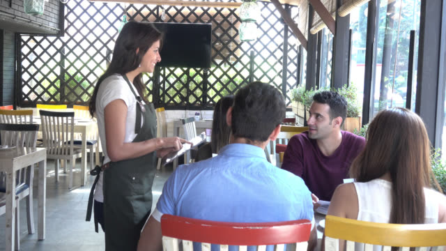 Beautiful waitress taking the order of a group on a tablet video