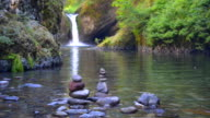 Beautiful waterfall above tranquil lake with stacked stones video