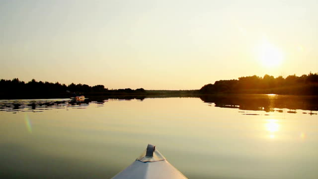 Beautiful waterscape, tourists paddling kayak at sunset video