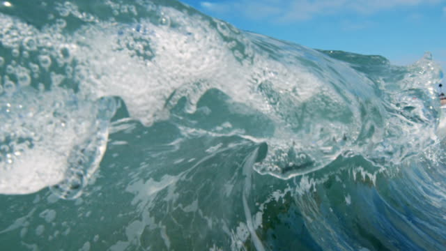 A beautiful wave POV as wave breaks over camera on shallow sand beach in the California summer sun. Shot in slowmo on the Red Dragon at 300FPS. video