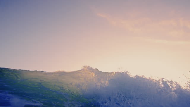 Beautiful wave POV as wave breaks over camera on shallow sand beach in the California sunset. Shot in slow motion. video