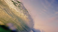 Beautiful wave POV as wave breaks over camera on shallow sand beach in the California summer sunset. Shot in slowmo. video