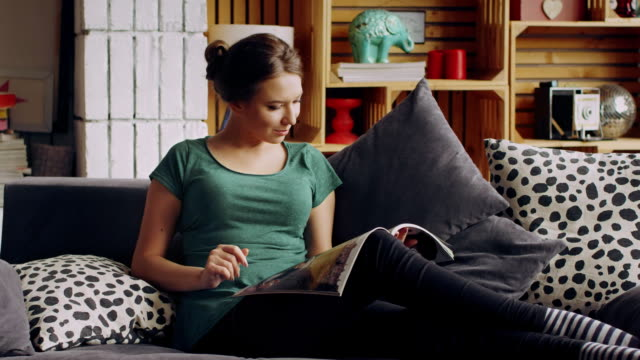 Beautiful well-groomed woman reading a fashion magazine lying on the sofa in the living room video