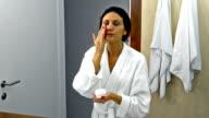 Beautiful woman applies skin moisturizer on her face video