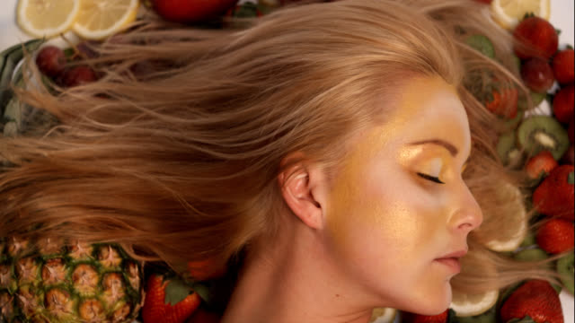 Beautiful woman asleep then awakens on a bed of fruit video