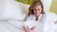 Beautiful woman at a hotel reading a book video