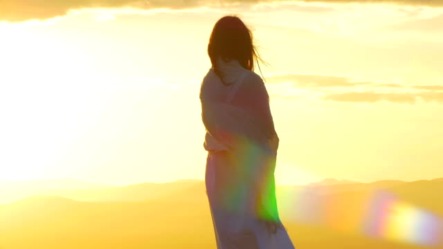 beautiful woman at the sunset on the top of a mountain with lens flare video