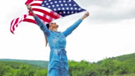 Beautiful woman carring U.S. flag with wide open hands video