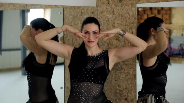 Beautiful woman dances oriental dance at mirror video