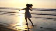Beautiful woman dancing and spinning on wet sea shore during sunset video