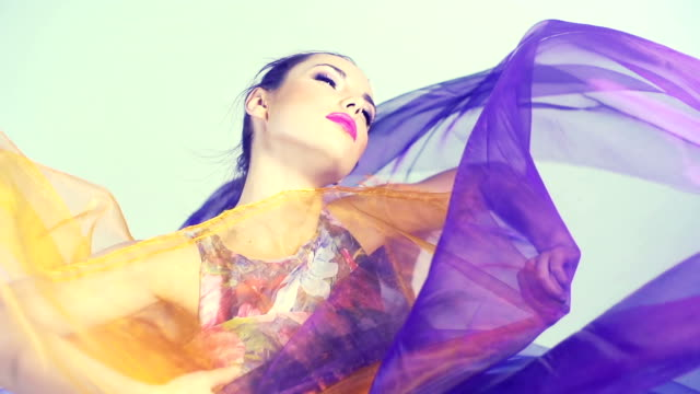 Beautiful woman dancing in colored silk. Slow motion. video
