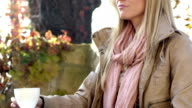 Beautiful woman drinking coffee in outdoor cafe video