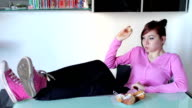 beautiful woman eating sweets relaxed with his feet on the table video
