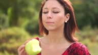 HD DOLLY: Beautiful woman eats an apple in the park video