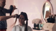 Beautiful woman enjoying while making a hairstyle at hairdresser's. video