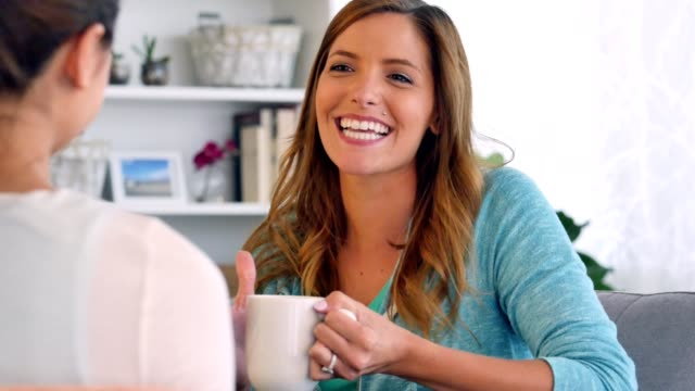 Beautiful woman enjoys a cup of coffee with her friend video