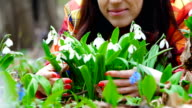 A beautiful woman enjoys blossoming snowdrops in a spring forest video
