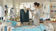Beautiful Woman Fashion Designer Adjusts Blouse on a Mannequin, Uses Her Smartphone and Smiles. Her Studio is Bright and Sunny, Clothes Hanging, Colourful Fabrics Lying on the Table. video
