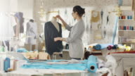 Beautiful Woman Fashion Designer Working with Tailoring Mannequin, Adjusting Blouse. Her Studio is Bright and Sunny, Mannequins Standing around, Clothes Hanging, Colourful Fabrics Lying on the Table. video