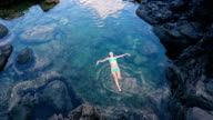 Beautiful Woman Floating on Back in Tide Pool. Relaxation in Nature. video