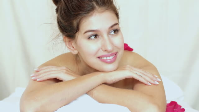 Beautiful woman for relaxing in spa with rose on back. video