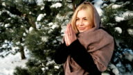 Beautiful woman heats hands, snow covered coniferous forest video