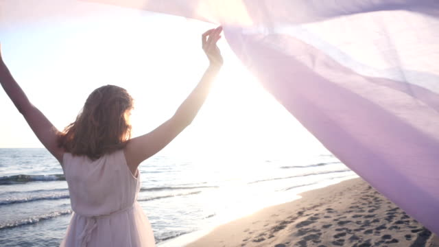 Beautiful woman holding light fabric on the beach and enjoy the sunset video