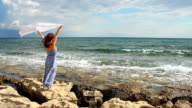 Beautiful woman holding scarf, standing on rocks, strong woman enjoying video