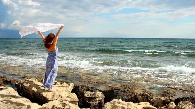 Beautiful woman holding scarf, standing on rocks, strong woman enjoying video