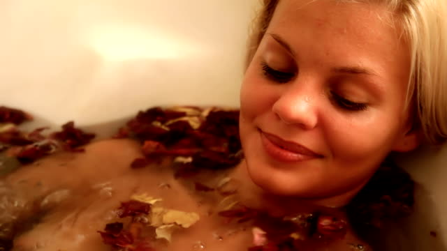 Beautiful woman in jacuzzi with flower petals video