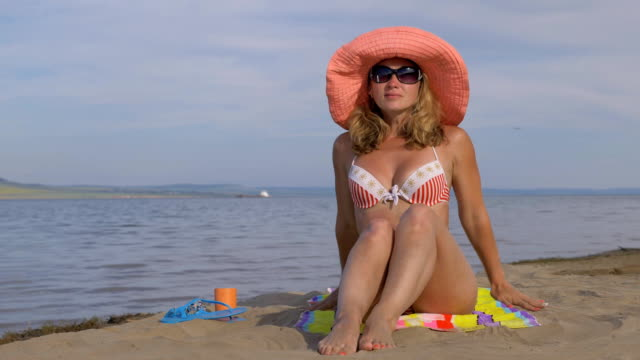 Beautiful woman is resting on the beach and looking at the sea. video