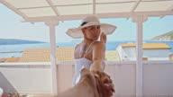 SLO MO Beautiful woman leading her boyfriend on the balcony video