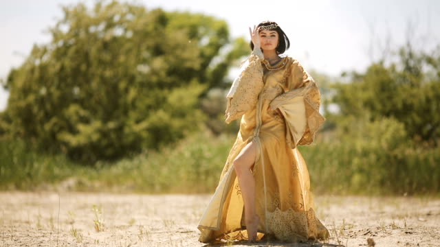 Beautiful woman like Egyptian Queen Cleopatra on in desert outdoor video