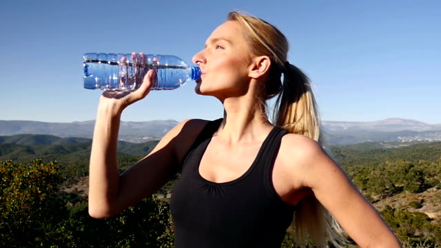 Beautiful woman looking away and drinking water video