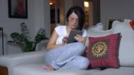 beautiful woman looking pad on sofa at home video