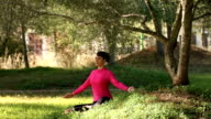 Beautiful woman meditating in  the park video