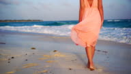 Beautiful woman on summer holidays on white beach. Close-up female legs. SLOW MOTION video