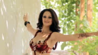 Beautiful woman professionally dancing oriental dance in nature, in slow motion video