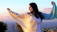 beautiful woman relaxing at the sunset in a countryside landscape video