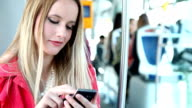 Beautiful woman riding tram, typing on mobile video
