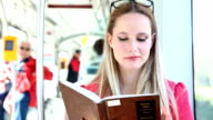 Beautiful woman riding tram, while reading book video