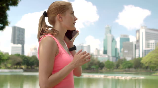 Beautiful woman runner jogging in park. Fit female sport fitness training. Talking on her smartphone video