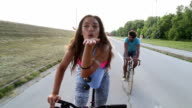 Beautiful woman sending kisses while cycling with friends video